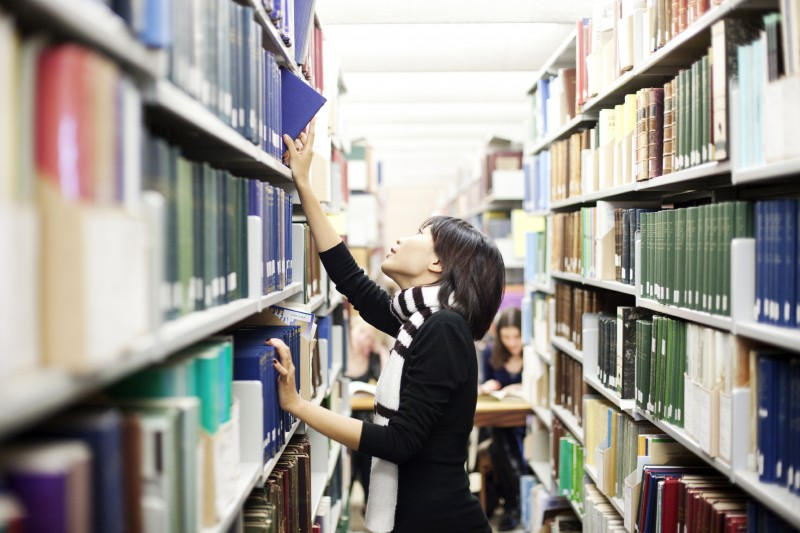 Girl taking a file from a library shelf